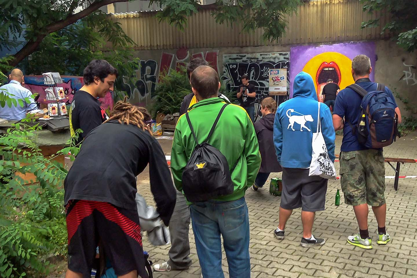 Visitors by the Painting of a tongue by Street Artist Jimmy C. aka. James Cochran in Berlin