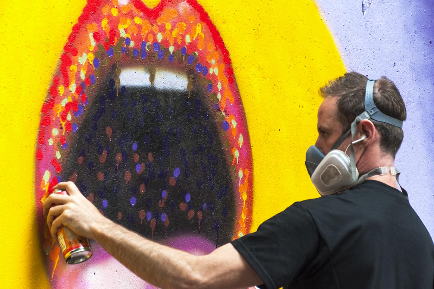 Close Up of Jimmy and the Painting of a tongue by Street Artist Jimmy C. aka. James Cochran in Berlin