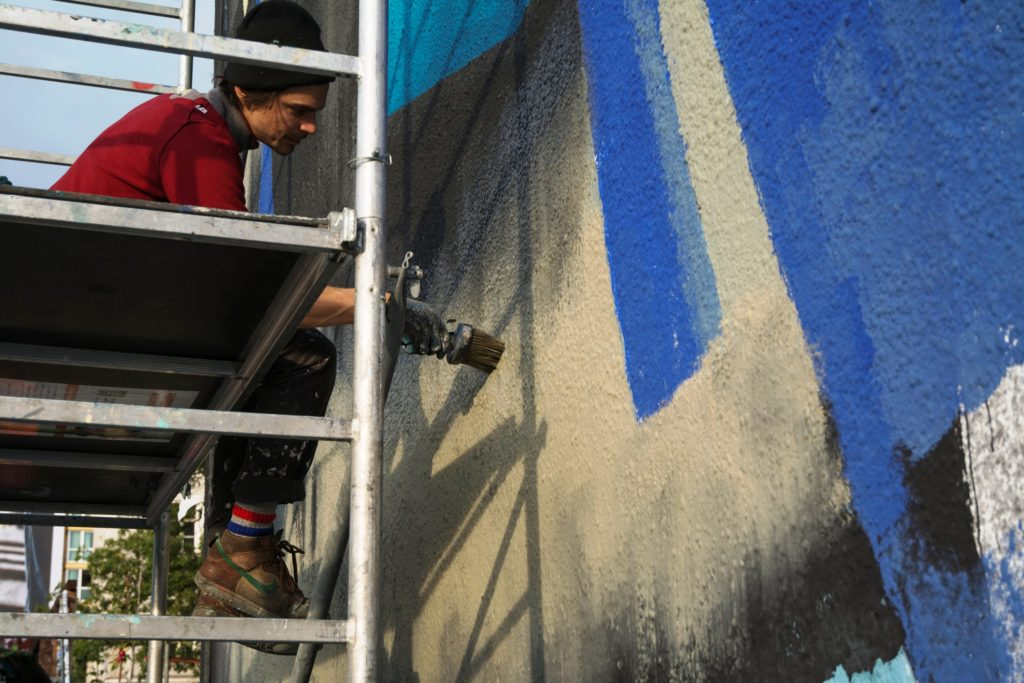 Detail of the artist painting his mural
